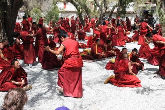 Debatterende monniken met handgeklap op de binnenplaats van het Sera klooster(1419)-1170